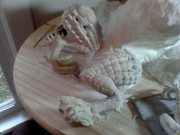 The ridges are added to the legs of the Dragon, and they are grouted with drywall compound in order to pull the detail together and finalize the sculpting on the legs.